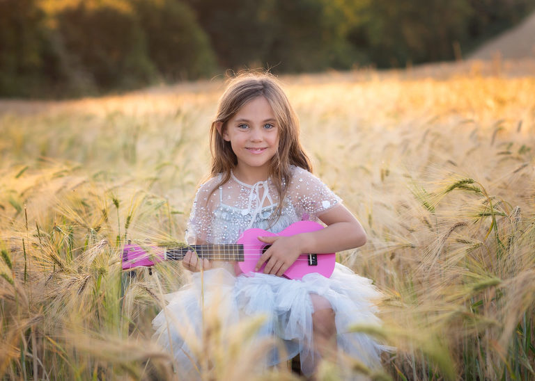 Girl playing guitar in the cornfields